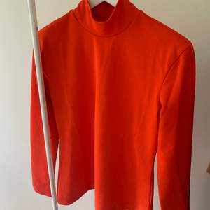 Röd härligt topp med krage perfekt nu när det bli kallare ute. Från H&M. Dragkedja baktill. Storlek: M.  Pris: 100 + 66kr.  95% polyester 5% elastan. Använd ett fåtal gånger så fint skick och inget att anmärka på