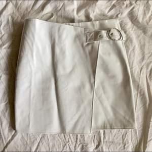 Vit kjol i lack i storlek 38. Snygg spännedetalj med osynlig dragkedja vid sidan. Liten fläck längst ner (se bild) men syns inte när man använder den