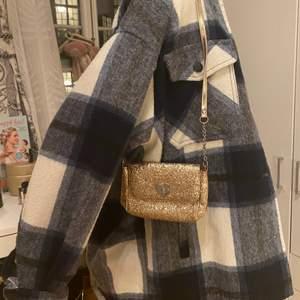Säljer dennna söta glittriga och trendiga axelväskan från H&M:)