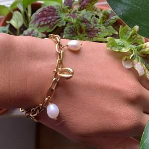 """Sprillans nytt Guldpläterat armband från """"bud to rose"""". Smyckat med berlocker i form av snäckor, blad och äkta sötvattenspärlor. Storleken är justerbar"""