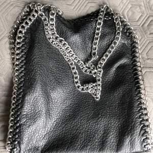 En svart väska med silverkedja. Den är rymlig och har inga fel eller skador! Använd några få gånger. Jättefin väska men använder inte så behövs säljas.