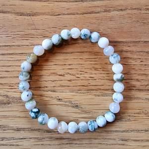 Armband med 6 mm stora kristallpärlor av trädagat.  Rundslipade stenar trädda på elastisk tråd. Ca 16 cm omkrets. Skickas i vadderat kuvert via postnord.