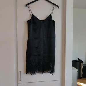 En svart sidenklänning med svarta spetsdetaljer från Mango i storlek S. Fraktkostnaden tillkommer.