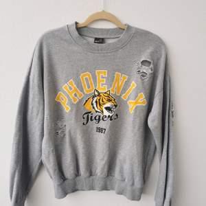 Riktigt cool sweatshirt med slitna hål. Givetvis meningen dom ska vara där. Grå botten med gul text och tiger på. Strl S. 150kr eller Bud. Köparen står för frakten och jag tar alltid 2 kr för emballage.
