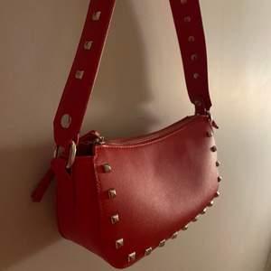 En väldigt snygg rödhandväska, stor inuti. Tillkommer med en silver kedja att ha så man kan ha den som axelväska. Nypris 300kr mitt pris 150kr. Köparen står för frakt