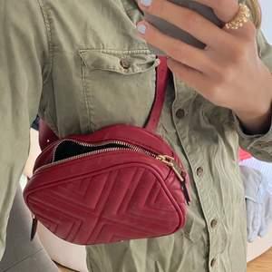 Vinröd väska som man kan ha i midjan eller crossover! Aldrig använd och den är från mango ❣️❣️ nypris 399kr