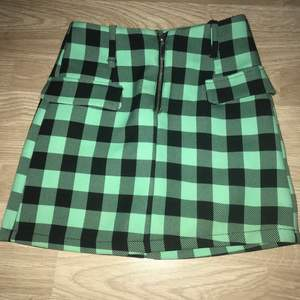 Grön och svart rutig mini kjol med dragkedja och fake fickor. Passar xxs-s
