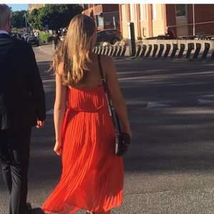 Världens finaste plisserade klänning i en orange färg åt det röda hållet. Endast använd en gång och galet snygg och skön. Halterneck och öppen rygg - funkar perfekt utan BH eller något sådant. Storlek S / 36.