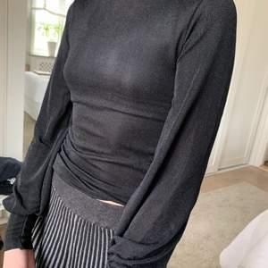 Glittrig svart tröja i mesh med ballongärmar o hög hals från Gina Tricot i stl XS🌞 använd ett fåtal gånger - tyvärr lite liten på mig😌
