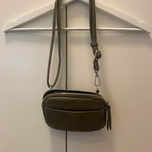 Frakten ingår inte i priset. Grön miniväska från Åhléns. Jag brukade använda den runt midjan. Använd men i bra skick.