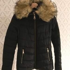 En svart dun jacka med päls krage (fake päls) jackan är använd men har inga skador som syns utåt, dock har den ett litet hål i vänstra fickan men inget man tänker på, jackan är varm och håller vind och kyla borta,   Köparen står för frakten✨✨ 300+frakt