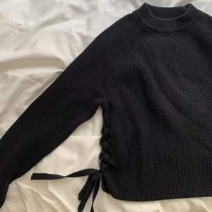 En snygg stickad tröja med knytning vid båda sidorna