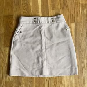 Beige kjol från HM med guldiga knappar och fickor på sidorna samt dragkedja bak.