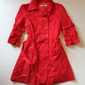 Röd trekvartsärmad kappa i tunt skjortmaterial, perfekt för våren/sommaren! Söt passform med midjeskärp och ballongärmar. Har använts endast någon enstaka gång, så är i prima skick!