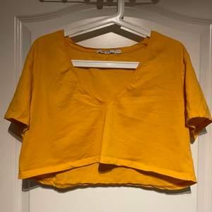 Senapsgul kort T-shirt med djup vringning från na-kd. Köparen står själv för fraktkostnaden.