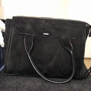 Svart stor väska som får plats med det mesta. I svart mocka. Dragkedjan är sönder på den, men går enkelt att fixa. Annars är den väl använd men i bra skick. ✨ Har även en lång rem att fästa så man kan ha den över axeln. Flera olika fickor/fack🌸 Pris kan diskuteras!