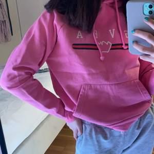 Rosa hoodie från Svea med luva och ficka.