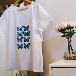 en vit oversize t-shirt med blå fjärilar, egensydd och aldrig använd!! köparen står för frakten