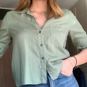 Säljer denna croppade gröna skjortan som är super fräsch nu till våren! Den är militärgrön med en ficka på ena bröstet. Säljer för 150 kr ink frakt!