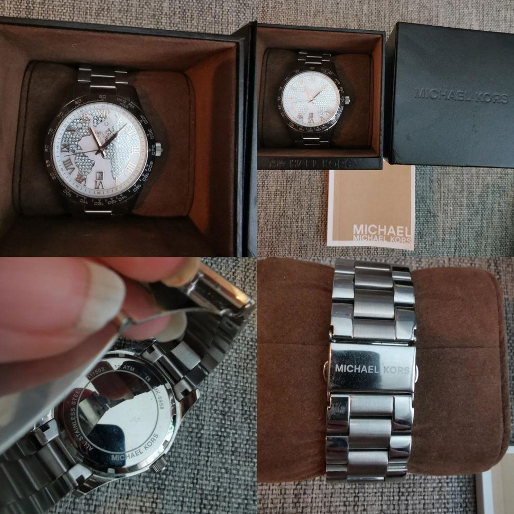 Fin äkta Michael kors klocka knappt använd. Silver med världskarta i strass. Kommer med alla tillbehör.. Accessoarer.