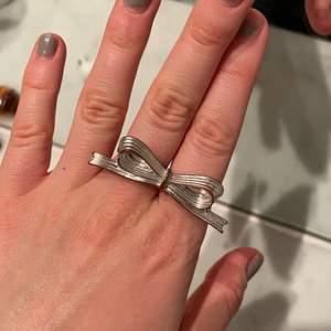 Rosett ring som är på två fingrar. Den har tyvärr blivit lite röd, men är fortfarande väldigt fin