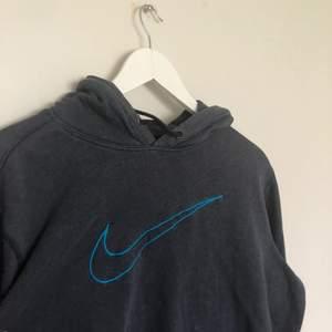 Vintage Nike Hoodie med en broderad swoosh logga på bröstkorgen. Storlek Medium och mörkgrå färg. Hoodien är i vintage skick med hål på vänstra armen. (Sista bilden)