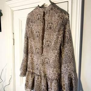 """Söt klänning med """"bohemiskt"""" mönster, beige/kall 'smutsrosa' med hög hög hals och söta volanger i kjolen och ärmarna. Aldrig använd! Från H&M!  Knappar i bak. Lapp kvar."""