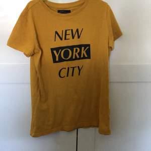 En gul tröja med svart text på framsidan är lite oversize så skulle säja en S