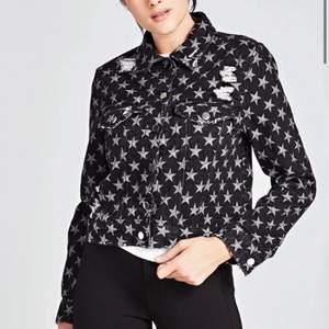 Supersöt jeansjacka från Guess. Den har slitningar och är svart/grå med stjärnor. Silvriga knappar och perfekt till våren och sommaren!