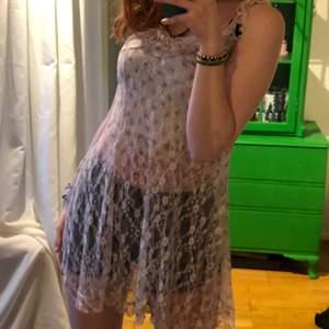 Unik och fin genomskinlig klänning med blommor och spets. Passar med en kjol under eller ett par jeans!