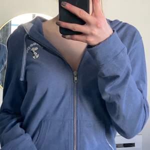 En blå snobben dragkedje hoddie, ser ut att vara en S men står att det är en L