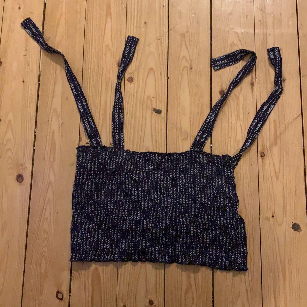 Kort blåt line med vit mönster  från Nelly med axel band som knyts själv i storlek L men mer M i storleken . Toppar.