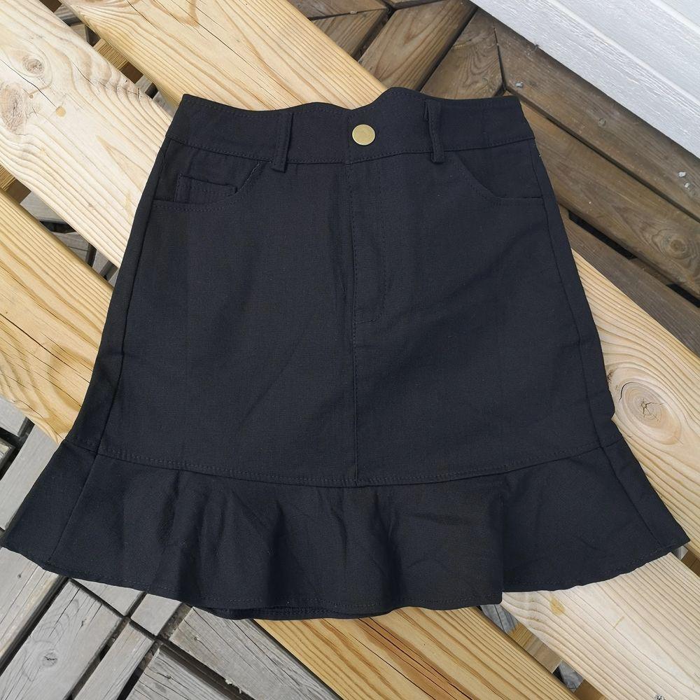 helt oanvänd svart kjol med volang-kant & guldknapp. väldigt liten I storleken, definitivt en XS även om det står M! Frkat:44kr. Kjolar.