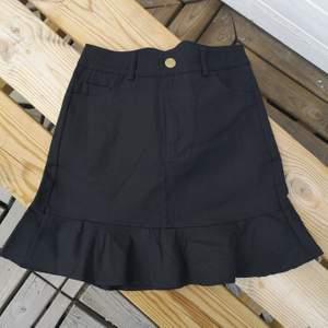 helt oanvänd svart kjol med volang-kant & guldknapp. väldigt liten I storleken, definitivt en XS även om det står M! Frkat:44kr