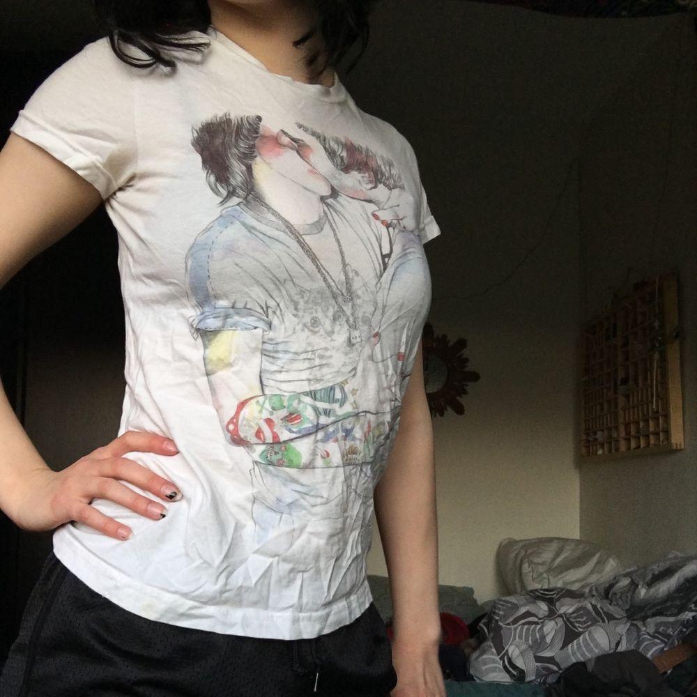 En skön secondhand vit T-shirt från T-POST med design som förseställer två personer som kysser varandra, om man vänder ut och in på t-shirten så står det lite om inspirationen till designen och om designern Esra Røise. Uppskattad storlek är S, Frakt 22 kr. T-shirts.