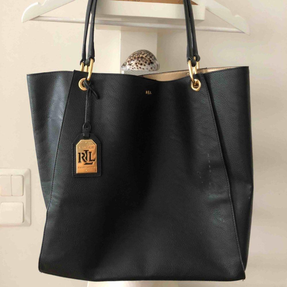 Rymlig skinnväska från Ralph Lauren med gulddetaljer, tyvärr litet märke på framsidan, därav pris men inget som stör och går säkert att fixa på något sätt. Väskor.