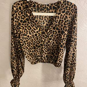 Blus med leopardtryck i storlek 36. Den har en v-ringning vid brösten och långa ärmar med fransiga manschetter vid ändarna. Använd fåtal gånger. Ordinarie pris: 249kr🌸