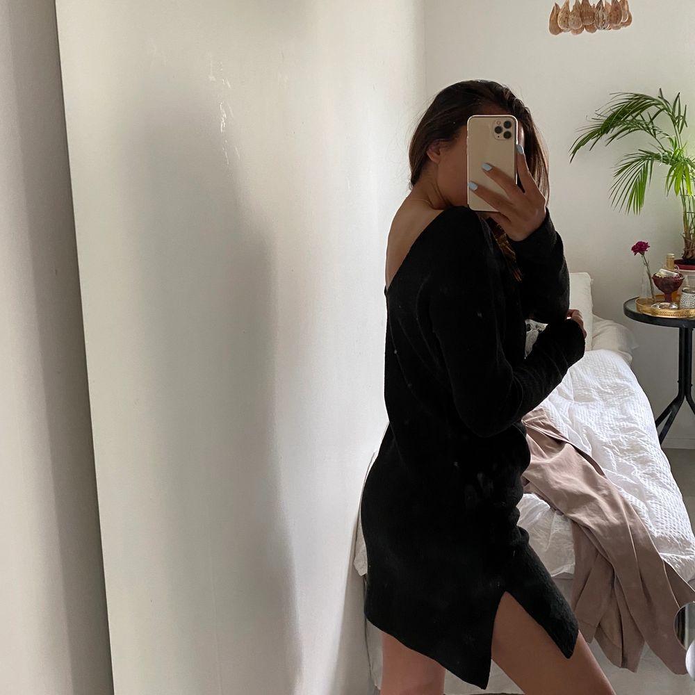 Stickad klänning i svart med djup rygg och slits på båda sidor.. Stickat.