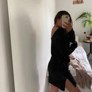 Stickad klänning i svart med djup rygg och slits på båda sidor.