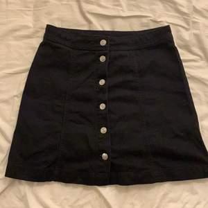 Svart hm kjol med knappar i mitten. Nypris 200. Använd 1 gång