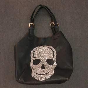 """Väska köpt i Spanien med skalle av diamanter på. Svart fake läder. En tillhörande axelband, dock har ena """"klämman"""" på det bandet gått sönder men det går nog att fixa! Går att kroka på annat axelband. Finns en """"liten väska"""" i väskan som är avtagbar."""
