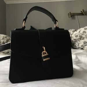 Jättegullig svart väska med guld detaljer Använd 2 gånger så ny skick💗 5 olika fack och två handtag, köparen står för frakt!