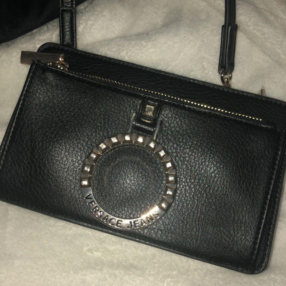 Versace Jeans väska, aldrig använd plasten i väskan är kvar från köpet. Köpt för 2 år sen men bara legat i garderoben sen dess, orginalpriset är 1799kr. Frakten är inkluderat i priset. Väskor.