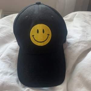 Super söt smiley keps! Endast använd ett fåtal gånger, inga defekter. Velcro-spänne i bak. Frakt ingår!