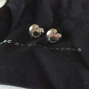 Marc by Marc Jacobs örhängen. Klassisk modell av silvriga hjärtan med märket i en ring. Tyvärr tål jag inte Marc Jacobs örhängen och säljer därför dessa.