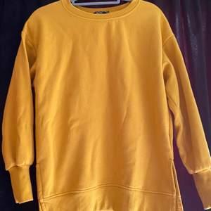 Senapsgul sweatshirt, knappt använd. Lite längre och med en slitts på sidan. Säljer pga kommer ej till användning.