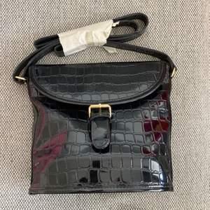 """OANVÄND, retro väska från 90-talet 🔥 Helt svart med fint """"print"""" av krokodilskinn (?) såklart EJ äkta skinn 🌟 Dekorativt spänne, den stängs alltså med magnet (se bild 2) ✨ Har ett litet fack med dragkedja 🤩  Köparen står för frakt, hör av er vid frågor 😊"""