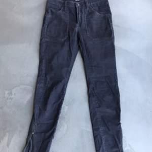 Lilaaktiga lowwaist tighta manchesterbyxor med dragkedjor vid anklarna. Har även bakfickor.