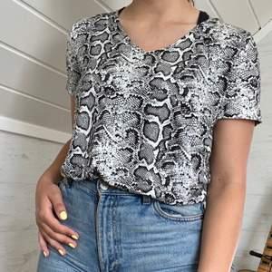 Ormskinnsmönstrad V-ringad T-shirt köpt på New Yorker för ca 1 år sedan. Märke: Amisu. ALDRIG använd så bra skick! Pris kan diskuteras.