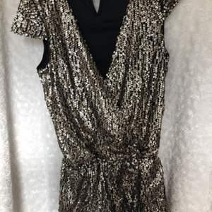 Guldig byxdress/playsuit, svart linne som sitter innanför för att den inte ska bli för urringad, fint skick och fint material. Storleken är 158, vilket motsvarar XS/S.